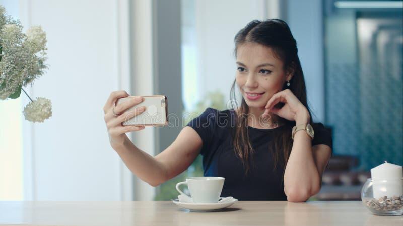 Lächelnde junge Frau, die selfies an ihrem Telefon am Café nimmt lizenzfreies stockbild