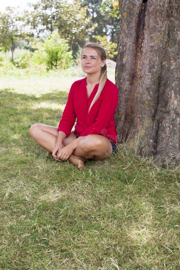 Lächelnde junge Frau, die Sommerfrische unter einem Baum genießt lizenzfreie stockfotos