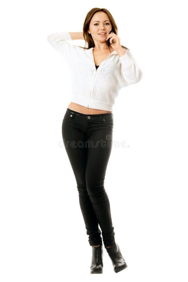 Lächelnde junge Frau, die am Telefon spricht stockfotografie