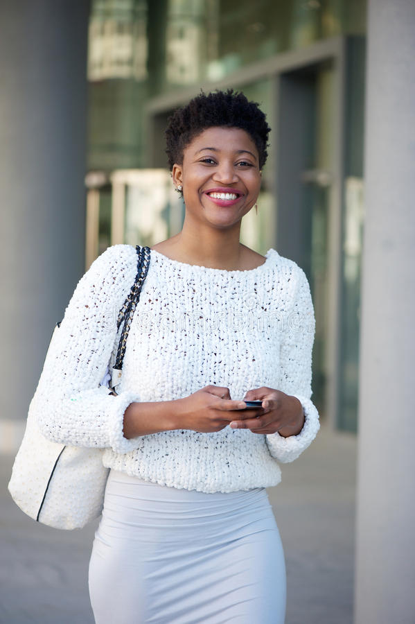 Lächelnde junge Frau, die Textnachricht int ihn Stadt schickt lizenzfreie stockbilder