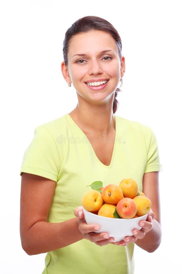 Lächelnde junge Frau, die volle Schüssel mit Aprikose hält lizenzfreie stockfotos