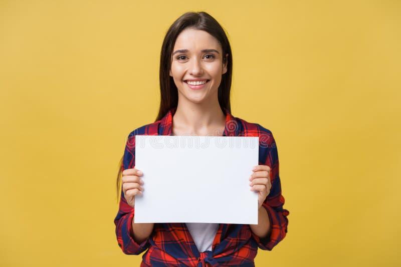 Lächelnde junge Frau, die Weißbuchblatt hält Studioporträt auf gelbem Hintergrund lizenzfreie stockbilder
