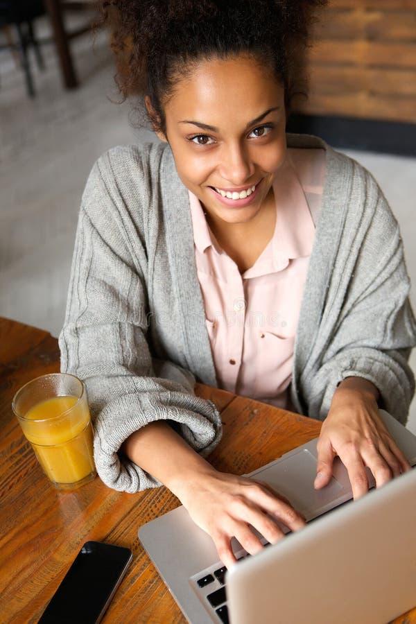 Lächelnde junge Frau, die zu Hause Laptop verwendet lizenzfreie stockfotografie