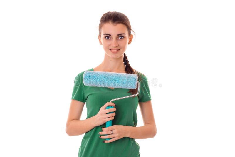 Lächelnde junge Frau in einem grünen Hemd hält nahe selbst Rolle für malende Wände stockfotos