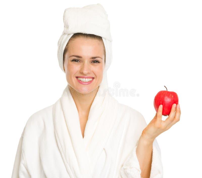 Lächelnde junge Frau im Bademantel mit Apfel lizenzfreie stockbilder