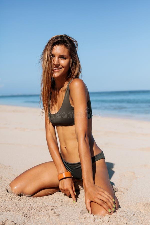 Lächelnde junge Frau im Bikini, der auf dem Strand sitzt stockfotos