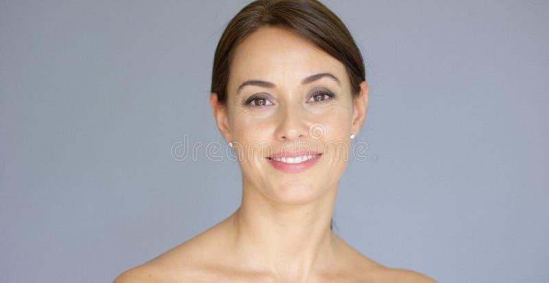 Lächelnde junge Frau im braunen Haar mit Kopienraum lizenzfreies stockbild