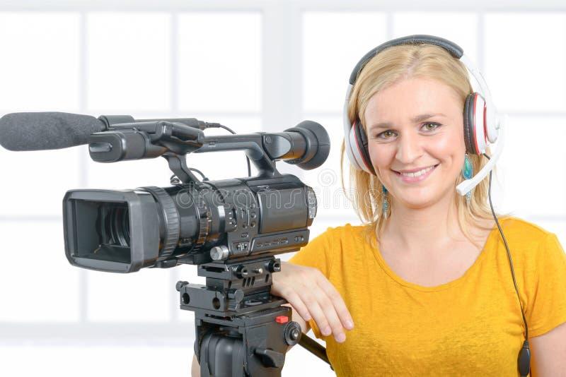 Lächelnde junge Frau im gelben T-Shirt mit Berufs-camcorde stockbilder