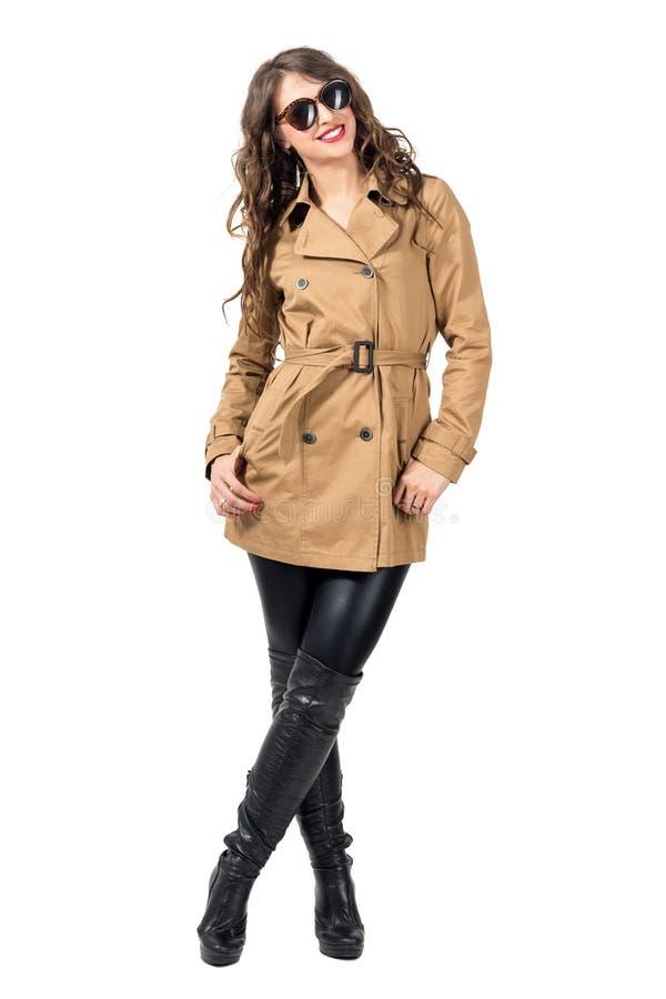 Lächelnde junge Frau im Herbst kleidet mit der Sonnenbrille, die zur Kamera sich lehnt und aufwirft lizenzfreies stockfoto