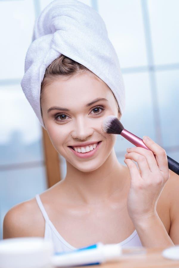 Lächelnde junge Frau im Tuchturban unter Verwendung der Pulverbürste lizenzfreies stockbild
