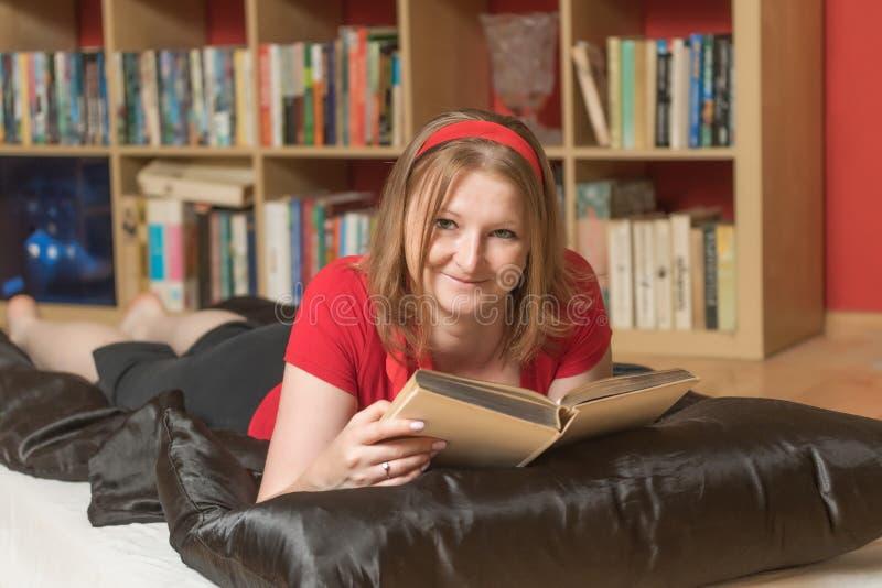 Lächelnde junge Frau liest ein Buch stockbild