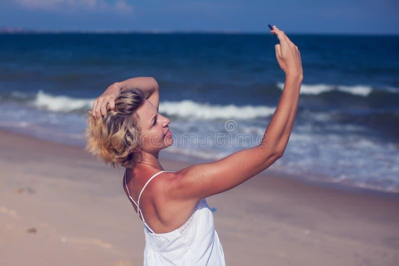 Lächelnde junge Frau machen ein selfie Foto am sandigen Strand durch das Se lizenzfreies stockbild