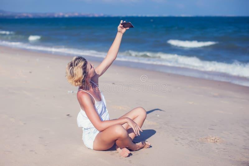 Lächelnde junge Frau machen ein selfie Foto am sandigen Strand durch das Se stockbilder