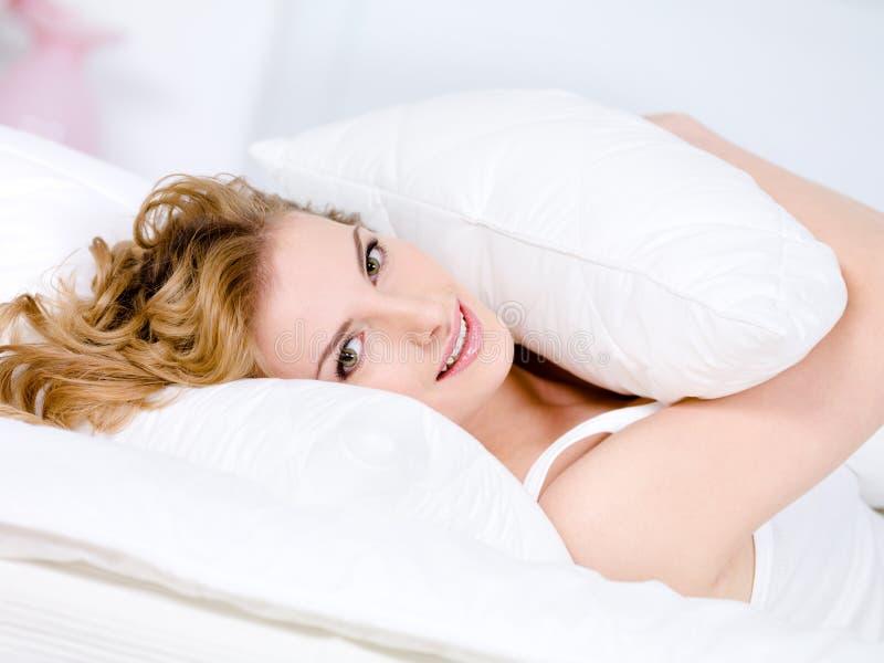 Lächelnde junge Frau mit dem entspannenden Kissen stockbild