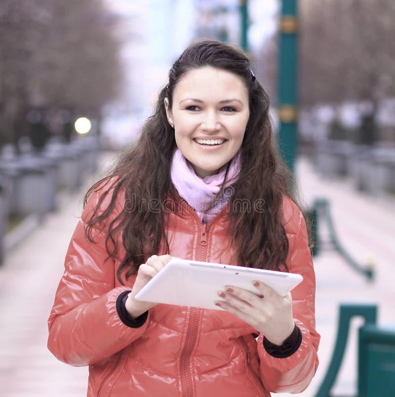 Lächelnde junge Frau mit der digitalen Tablette, die auf Stadtstraße steht stockfotos