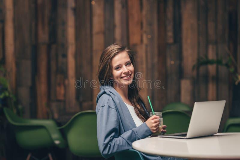 Lächelnde junge Frau mit Laptop stockbild
