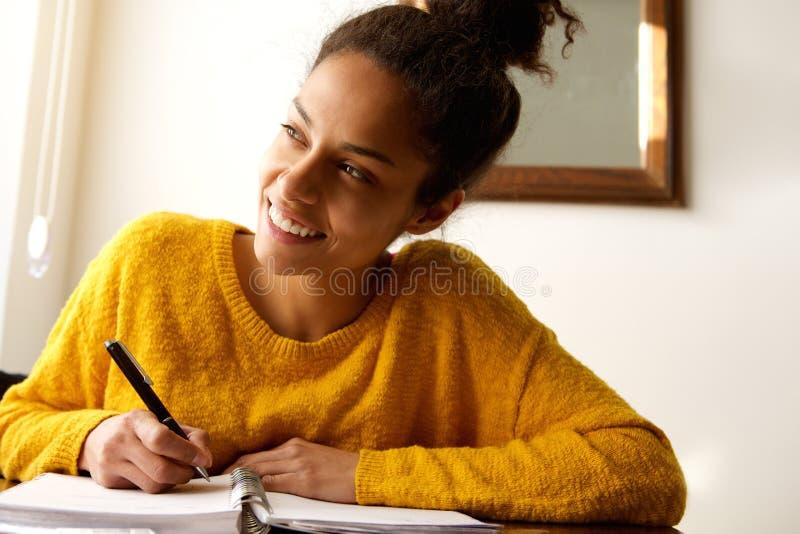 Lächelnde junge Frau mit Notizbuch und Stift am Schreibtisch lizenzfreies stockfoto