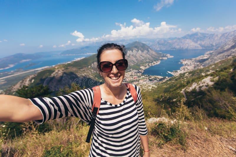 Lächelnde junge Frau nimmt ein selfie auf Hintergrundberg und -meer stockfoto