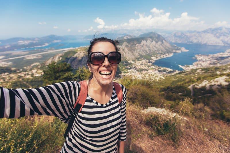 Lächelnde junge Frau nimmt ein selfie auf Hintergrundberg und -meer lizenzfreies stockfoto
