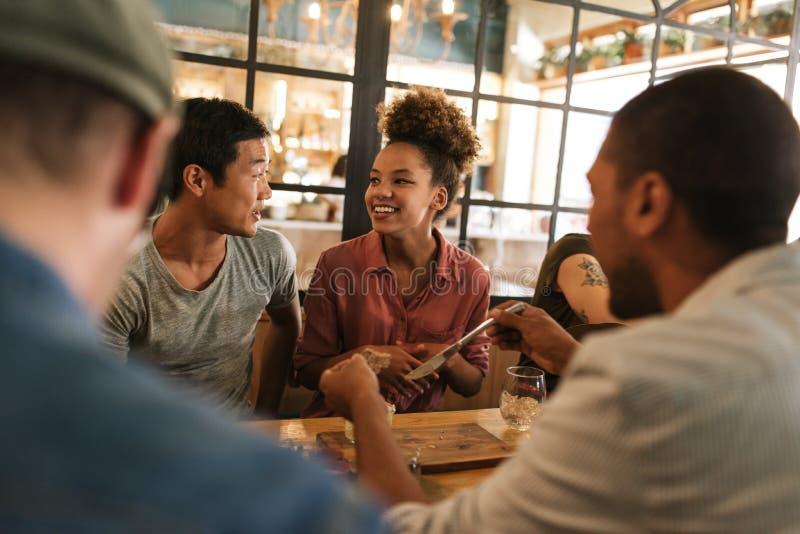 Lächelnde junge Freunde, die zusammen über einem Bistroabendessen sprechen stockfotografie