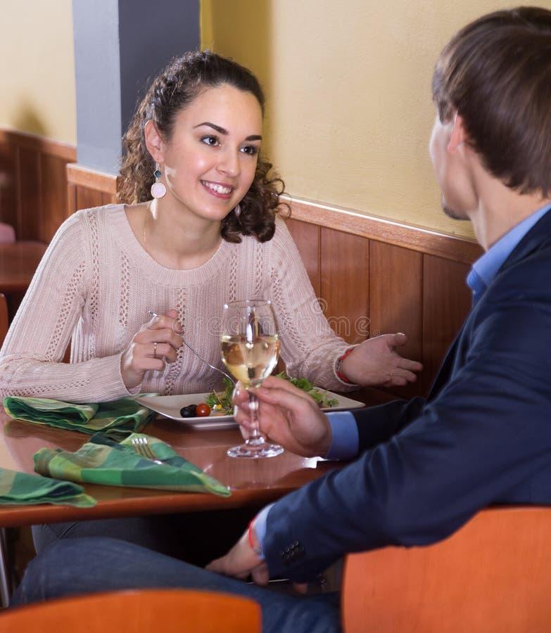 Lächelnde junge Gatten, die geschmackvolles Abendessen im Restaurant genießen stockbilder