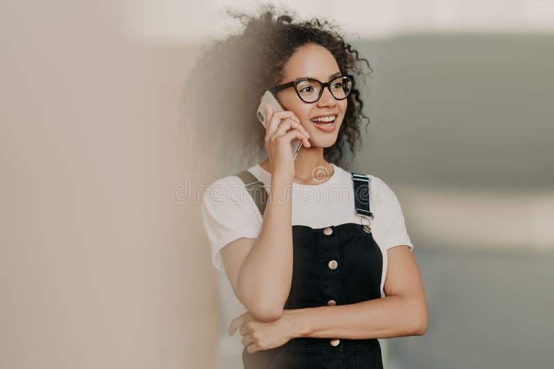 Lächelnde junge gelockte Frau mit leichtem Lächeln, Gespräche am Handy, hat freundliches Gespräch, trägt zufälliges weißes T-Shir lizenzfreie stockbilder