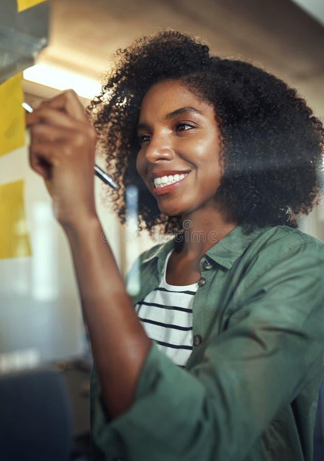 Lächelnde junge Geschäftsfrau, die auf klebende Anmerkung über dem gl schreibt stockbilder