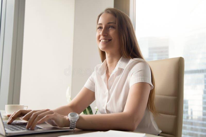 Lächelnde junge Geschäftsfrau, die den Laptop, herein arbeitend an Computer verwendet stockbilder