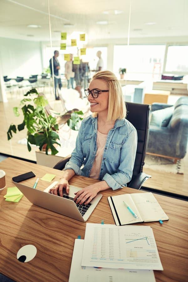 Lächelnde junge Geschäftsfrau, die einen Laptop an ihrem Schreibtisch verwendet stockfotos