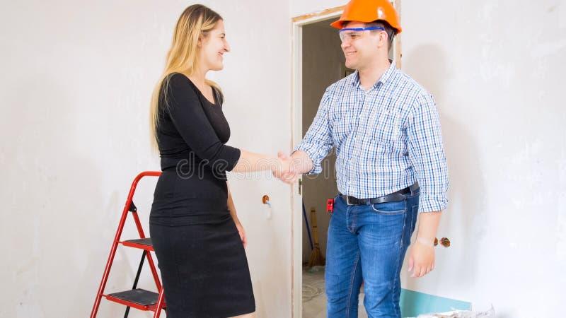 Lächelnde junge Geschäftsfrau, die Hände mit Auftragnehmer am Haus unter Erneuerung rüttelt lizenzfreies stockbild