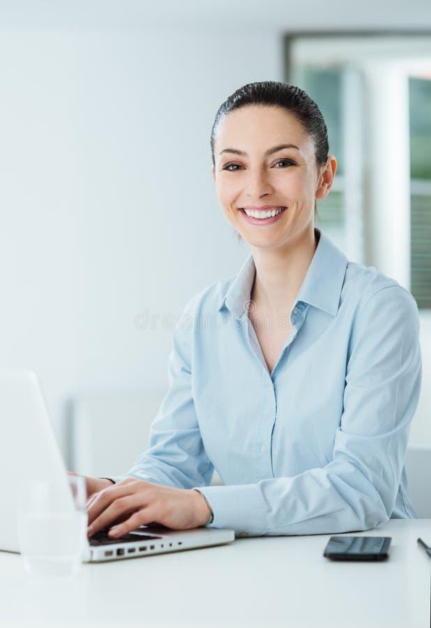 Lächelnde junge Geschäftsfrau, die am Schreibtisch arbeitet lizenzfreie stockbilder