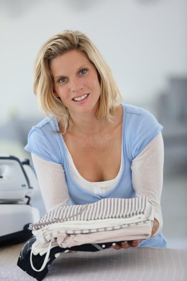 Lächelnde junge Haushälterin mit frisch gebügelter Kleidung stockfoto