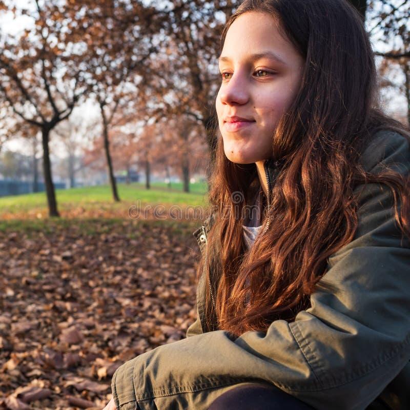 Lächelnde junge Jugendliche, die im Herbstpark sitzt stockfotos