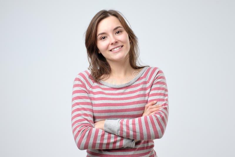 Lächelnde junge kaukasische Frau mit ihren Armen gefaltet stockfotos
