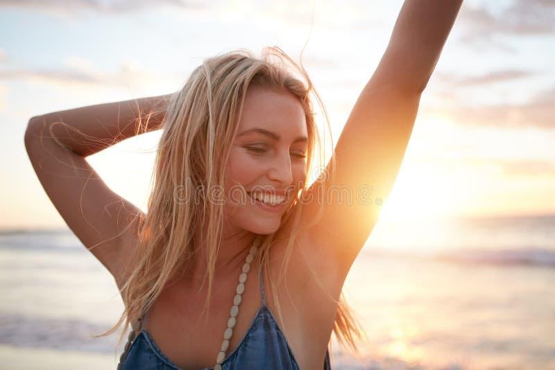 Lächelnde junge kaukasische Frau am Strand stockfotos