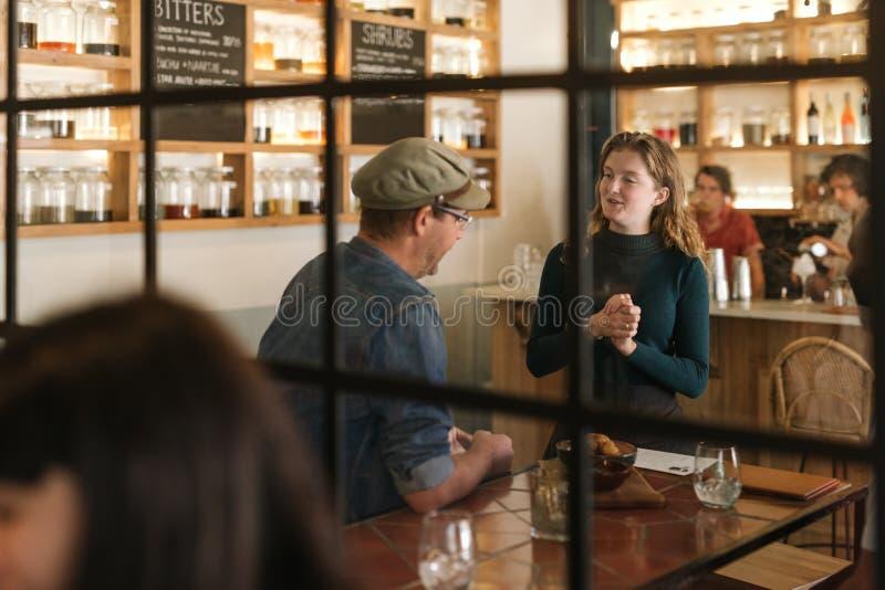 Lächelnde junge Kellnerin, die mit einem Bistrokunden spricht stockbilder