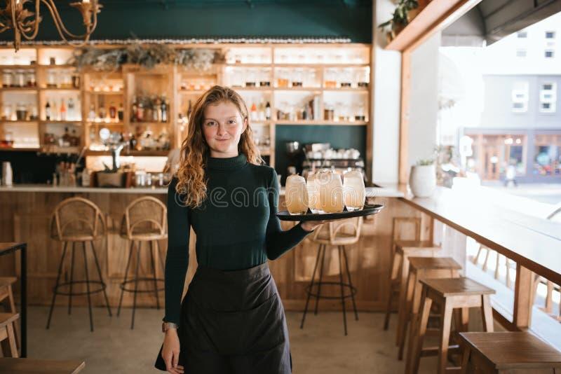 Lächelnde junge Kellnerinstellung mit einem Behälter von Getränken lizenzfreies stockfoto