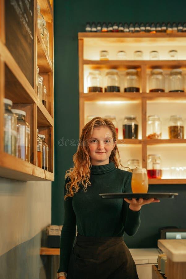 Lächelnde junge Kellnerinumhüllung trinkt in einer modischen Bar stockbild
