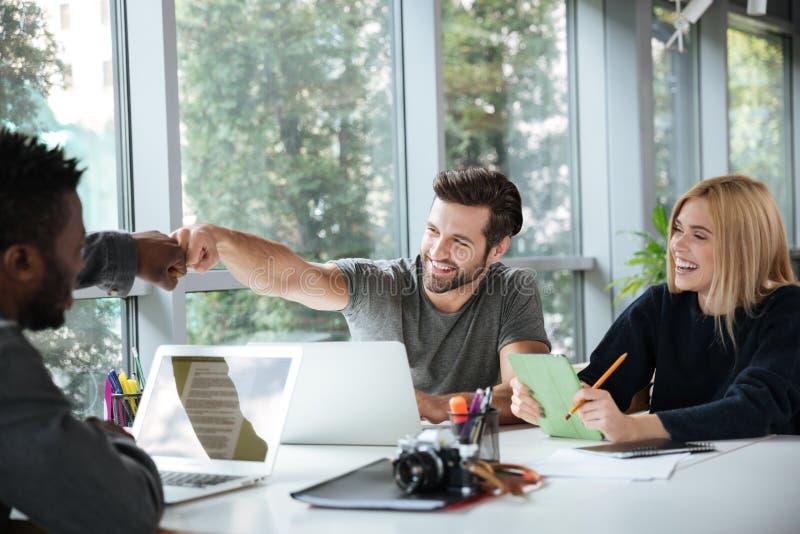 Lächelnde junge Kollegen, die im coworking Büro sitzen lizenzfreies stockbild