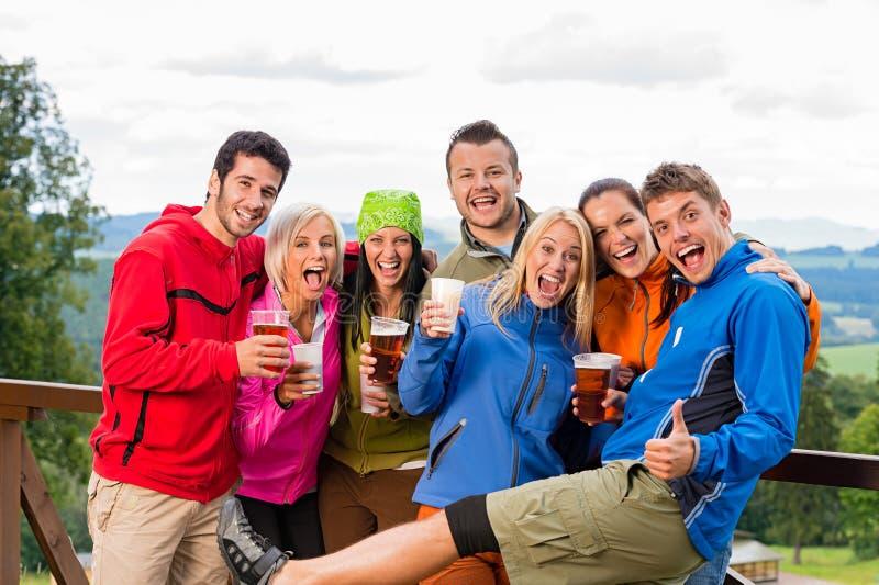 Lächelnde junge Leute mit Bier draußen aufwerfen stockfotos