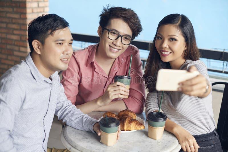 Lächelnde junge Mitarbeiter, die selfie in der Kaffeestube nehmen lizenzfreies stockbild