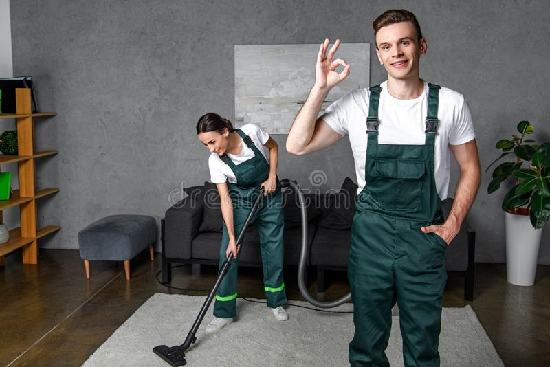 lächelnde junge Reinigungsfirmenarbeitskräfte, die das Staubsauger und Zeigen des O.K.zeichens verwenden stockbild