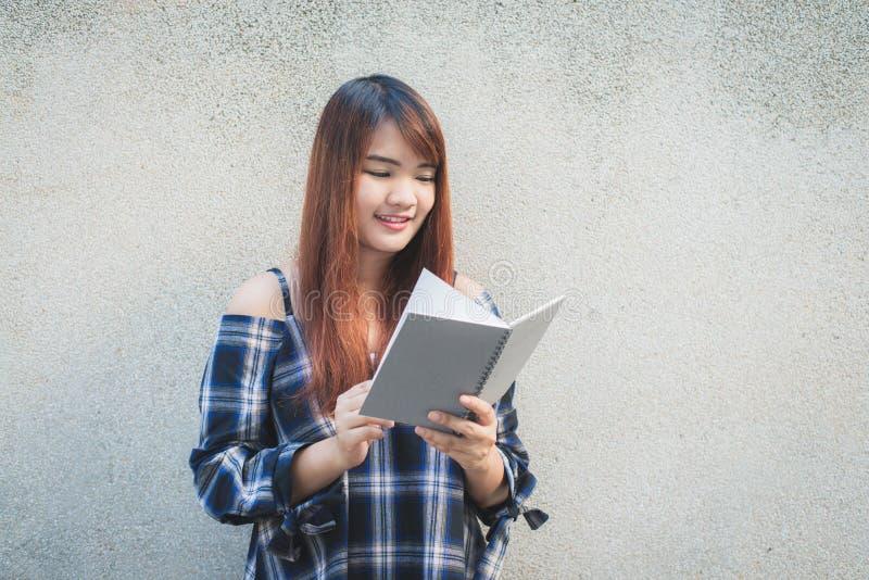 Lächelnde junge schöne asiatische Frauen mit Buch Braune schöne junge glückliche Hauptlesung der Frau der Nahaufnahme recht auf B stockfotografie