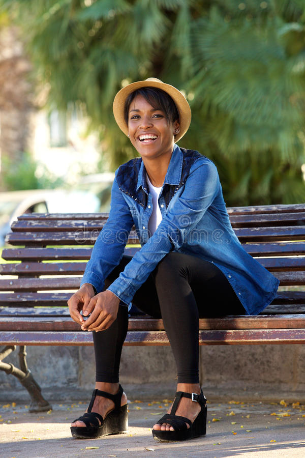Lächelnde junge schwarze Frau, die auf Bank am Park sitzt stockfotografie