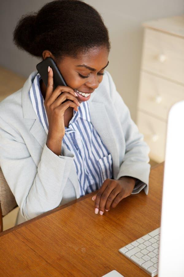 Lächelnde junge schwarze Geschäftsfrau, die im Büro spricht am Telefon sitzt stockfotografie