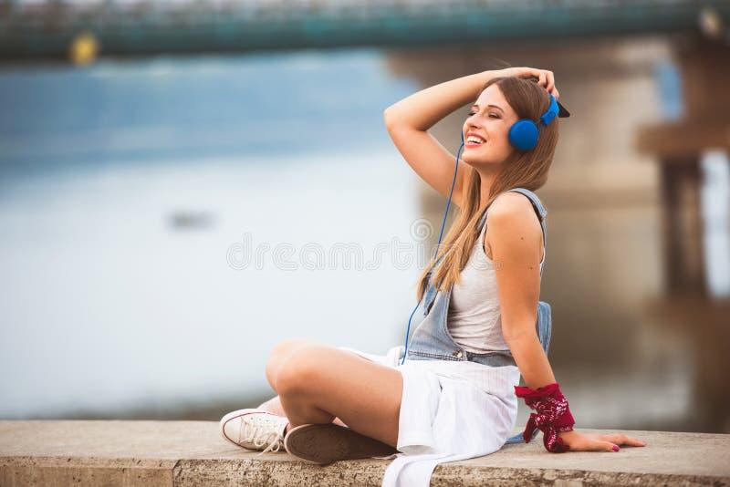 Lächelnde junge städtische Frau, die intelligentes Telefonfreien beim Warten auf ihre Freunde verwendet stockbild