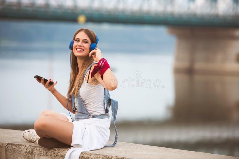 Lächelnde junge städtische Frau, die intelligentes Telefonfreien beim Warten auf ihre Freunde verwendet stockfoto
