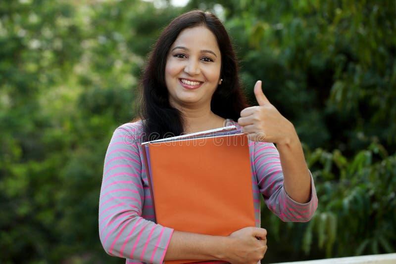 Lächelnde junge Studentin, die thumbsup Geste macht lizenzfreie stockfotos