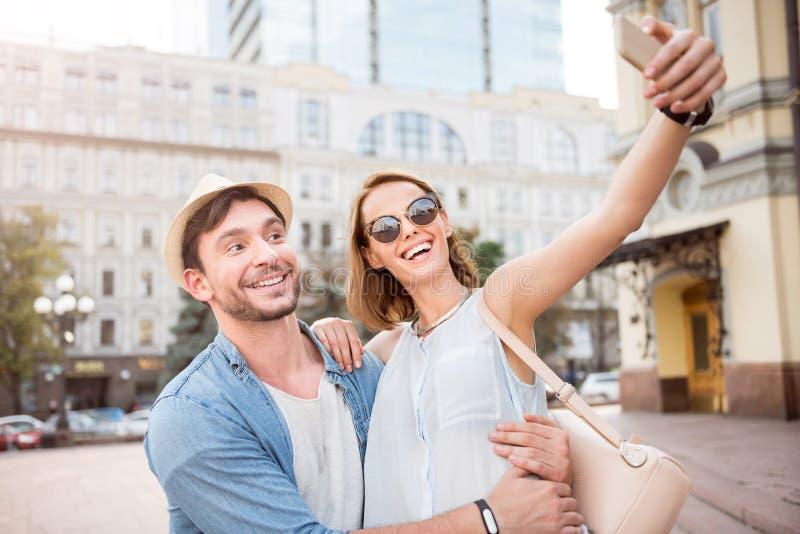 Lächelnde junge Touristenpaare auf einem Weg stockbild