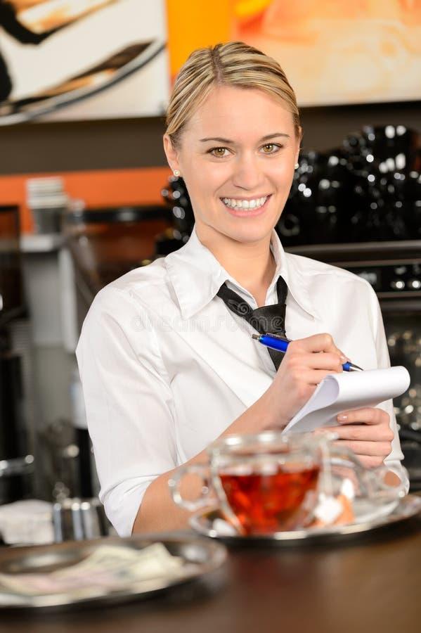 Lächelnde Kellnerin, die Auftrag im Kaffeehaus entgegennimmt lizenzfreies stockfoto